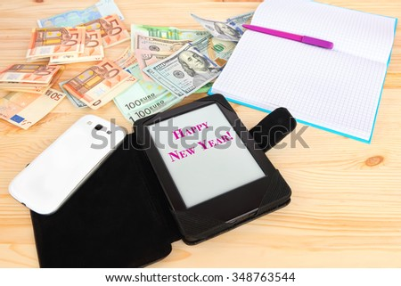 Modern gadgets tablet with Happy New Year greeting, smart phone and classic notebook. Money (banknotes euro and USA dollars) in the background. Modern gadgets and retro office accessories with money - stock photo