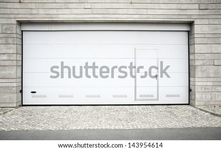 Modern garage door. Large automatic up and over garage door with inclusion of smaller personal door. - stock photo