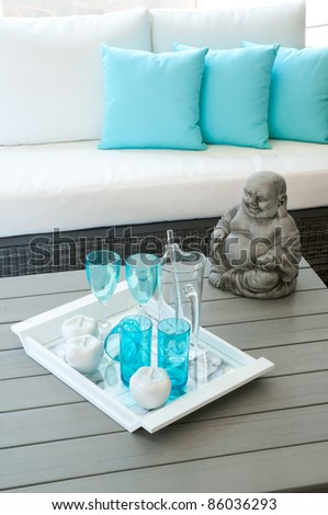 Modern garden furniture with Buddha statue on the table - stock photo