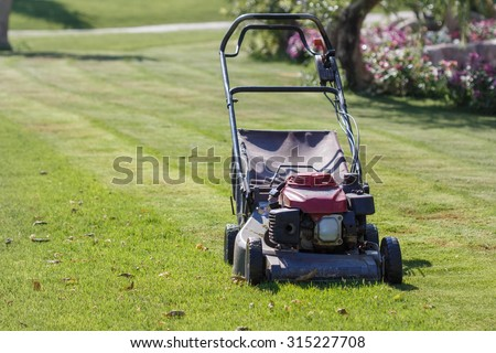 Modern gasoline lawn mower on a green meadow. Garden equipment - stock photo
