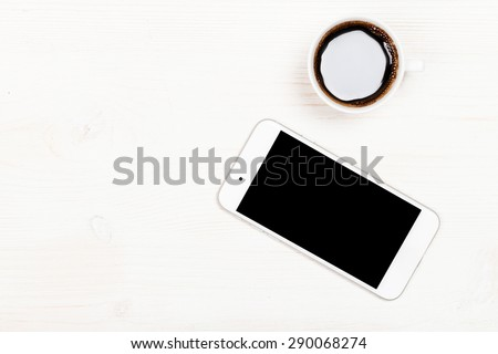 Modern generic smart phone with empty isolated white screen and coffe on a table.  - stock photo
