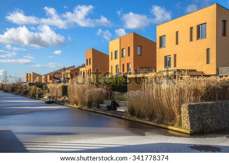 Modern geometric family houses along a canal in winter setting, Groningen, Netherlands - stock photo