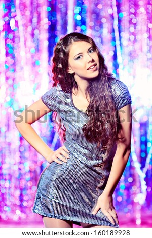 Modern girl dancing at the party. Disco lights. - stock photo