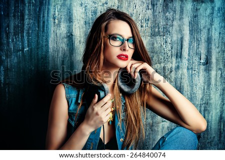 Modern girl in casual jeans clothes listens to music in headphones. Fashion. - stock photo