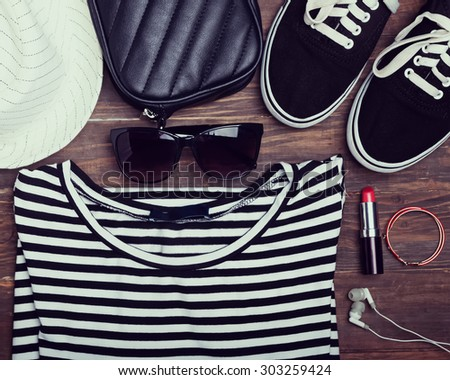 Modern girl outfit on wooden background, top view. Retro toned photo. - stock photo