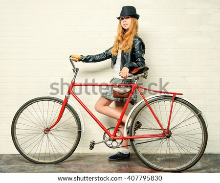 Modern girl teenager stands with her old bicycle by a brick wall.  - stock photo