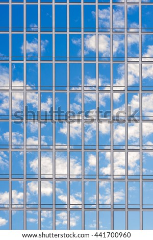 Modern Glass Building Reflecting Blue Sky and White Clouds during day. - stock photo