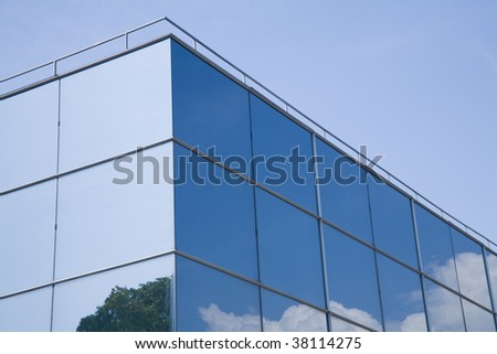 Modern glass building with trees and clouds reflected on it.