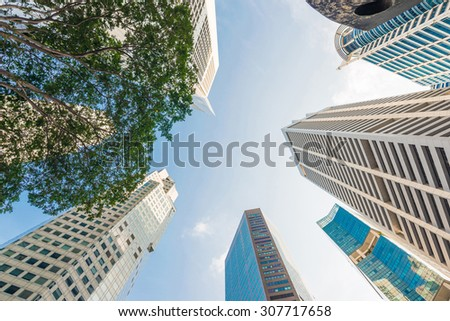 Modern glass city buildings during sunny day. Low angle shot - stock photo
