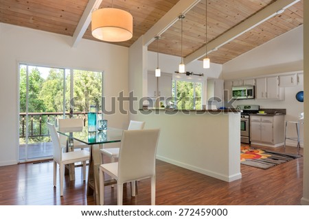 Modern glass dining table beautiful New kitchen in mid century home with cherry wooden floor and wooden ceiling. Kitchen in white with granite counter tops with stainless steel appliances. - stock photo