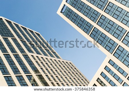 Modern glass high-rise office building with acute angles showing reflections of a bright blue clear sky. Nobody in the image and copy space area for business finance or architectural designs.