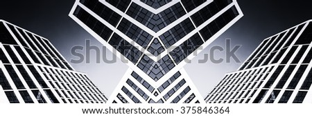 Modern glass high-rise office building with acute angles showing reflections of a bright blue clear sky in Monochrome. Toned black and white wall art using symmetry. - stock photo