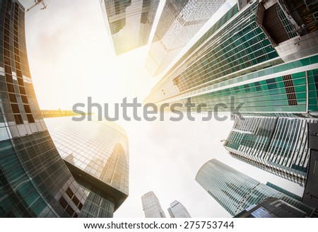 Modern glass silhouettes of skyscrapers in the city. Focus on the tops of skyscrapers - stock photo