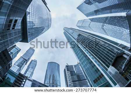 Modern glass silhouettes of skyscrapers in the city. toning photo. Focus on the tops of skyscrapers - stock photo