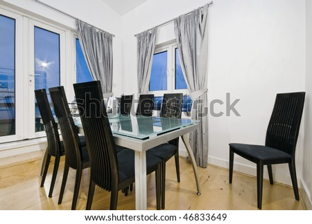 modern glass top dining table with black chairs and seats for eight