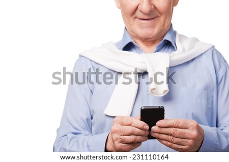 Modern grandfather. Happy senior man holding mobile phone while standing against white background  - stock photo