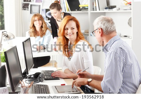 Modern graphic designer woman working with colleagues in office. Small business. - stock photo
