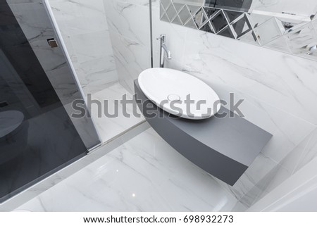 Modern gray bathroom with sink and shower tiled with white marble tiles