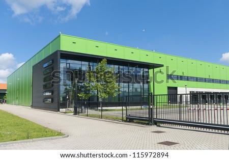 modern green warehouse in the Rotterdam harbor area - stock photo