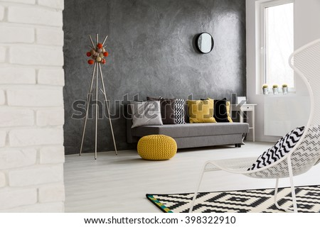 Modern, grey interior with sofa, chair, yellow details and stylish decorations   - stock photo