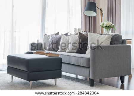 modern grey sofa with pillows and black table in living room at home - stock photo