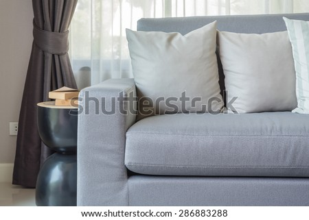 modern grey sofa with pillows in living room at home - stock photo
