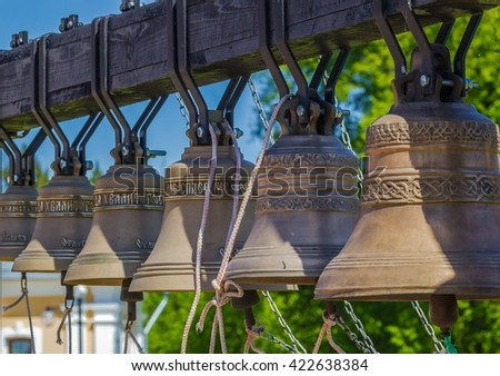 Modern ground belfry, a row of six metal bells, on which were written the words of the Orthodox prayers. - stock photo