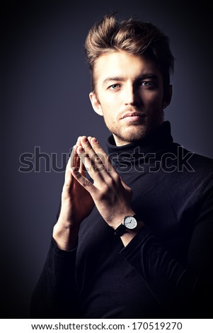 Modern handsome young man in black pullover posing over dark background.