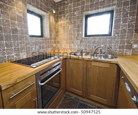modern hard wood kitchen unit with stone tiles - stock photo