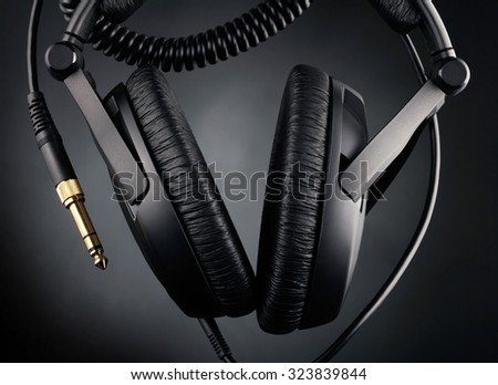 Modern headphones over black background - stock photo
