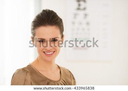 Modern health care. Happy young woman in front of Snellen chart - stock photo