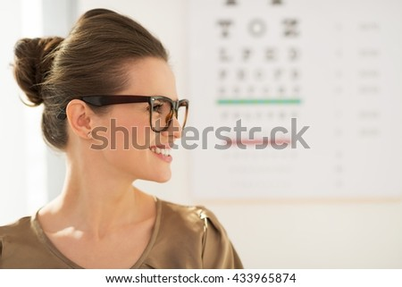 Modern health care. Profile portrait of happy young woman wearing eyeglasses in front of Snellen chart - stock photo
