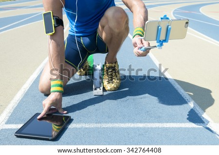 Modern hi-tech athlete crouching at the starting line of a running track wearing a fitness armband, multitasking between using a tablet, and taking a selfie with his smartphone. Focus on smartphone.