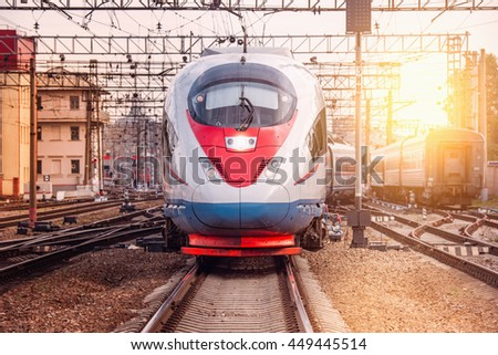 Modern high-speed train departs from the station at sunset. - stock photo