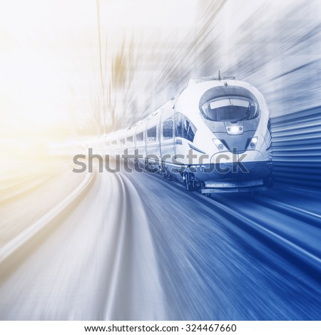Modern high-speed train moves fast at sunset time. - stock photo