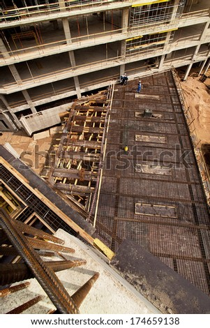 Modern high-tech factory formwork construction site with workers - stock photo
