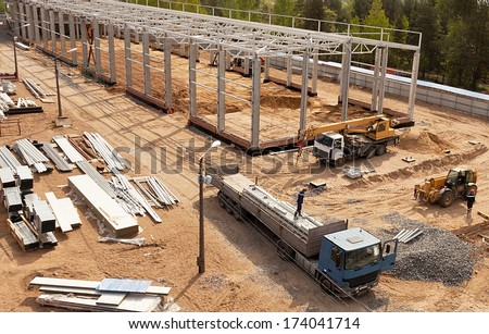 Modern high-tech factory formwork construction site with workers and trucks - stock photo