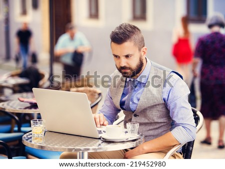 Modern hipster businessman drinking espresso coffee in the city cafe during lunch time and working on laptop - stock photo