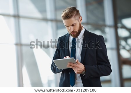 Modern hipster businessman working on digital tablet at office - stock photo