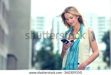 Modern hipster girl using a mobile phone. Young woman in the open space of the street of the city reads a message from a mobile phone.