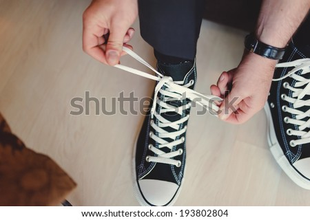Modern hipster wedding, groom wearing sneakers instead of classic elegant shoes, tying the laces and preparing. Vintage effect - stock photo