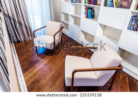 Modern home  interior. library with arm chairs.