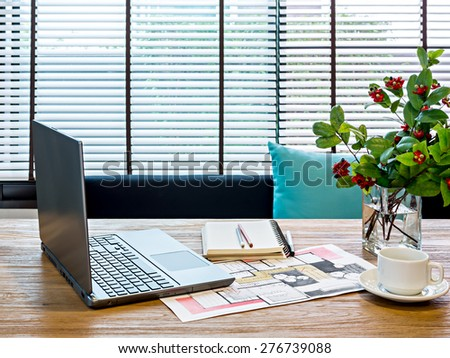 Modern home office workspace with laptop, architecture hand-drawn illustration on table - stock photo