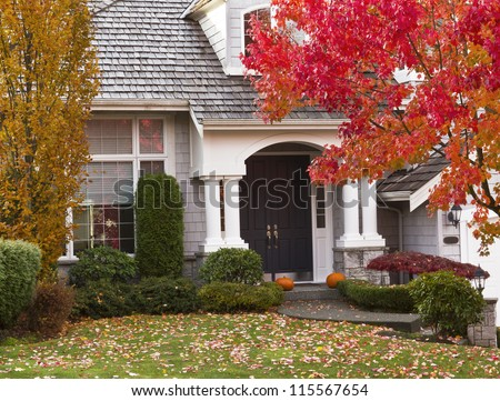 Modern home surrounded by autumn season with maple leaves on ground and trees turning bright colors - stock photo