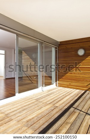 Modern home with sunny balcony of and wooden floor - stock photo