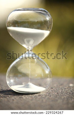 Modern Hourglass -- sand trickling through the bulbs of a crystal sand glass. every second counts. symbol of time. spring countdown.