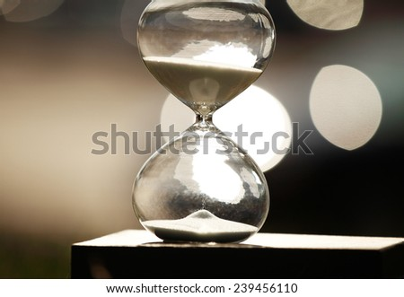 Modern Hourglass -- sand trickling through the bulbs of a crystal sand glass. every second counts. symbol of time. countdown.  - stock photo