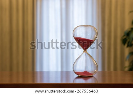 Modern Hourglass -- sand trickling through the bulbs of a crystal sand glass.  Every second counts. A symbol of time. - stock photo