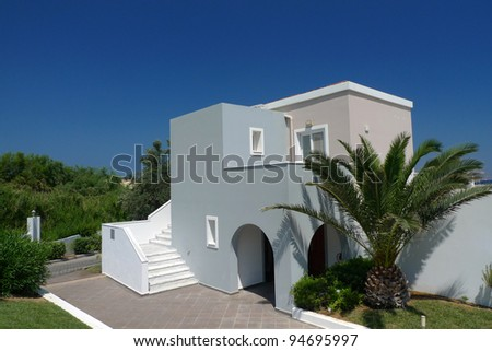 Modern house in the green with palm