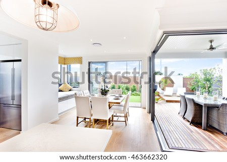 Modern house indoor outdoor areas close look at day time with sunlight from the outside garden area, there is a dining area next to the entrance beside a bed and patio place with table set up